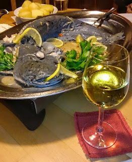 A plate with a catfish together with a glass of Riesling