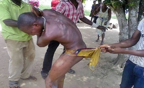 Caught in the Act: Angry Mob Beat and Strip Man N*ked for Snatching Woman's Handbag in Abuja (Photo)