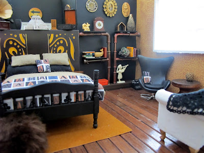 One-twelfth scale miniature scene, with a bed dressed in linen and black with throw rug and cushion printed with letter As, in front of a false wall. To the right is a lounge area with a set of pipe shelves, a black egg chair and a cream sofa.