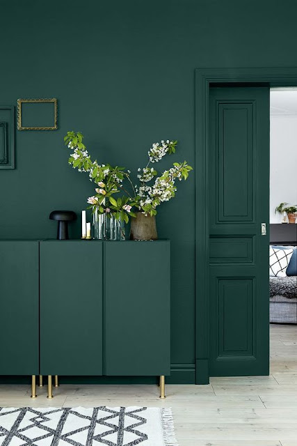 Deep teal walls and matching trim in living room on Hello Lovely