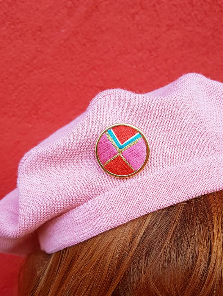 Red, pink, gold and mint embroidered pin worn on a pink beret