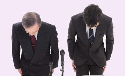 スーツを着た二人の男性が頭を下げて謝罪をしている
