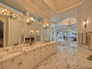 A well organised bathroom with everything in white like floor,walls and cabinets