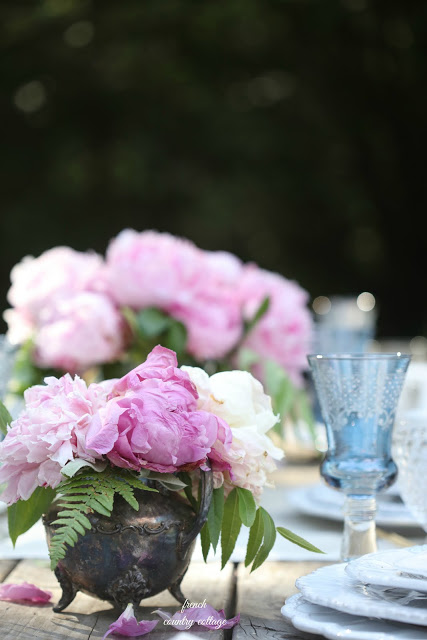 peonies in silver container with blue glass table setting