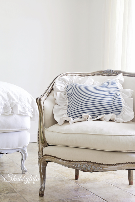 blue and white ticking stripe pillow on a french bergere chair