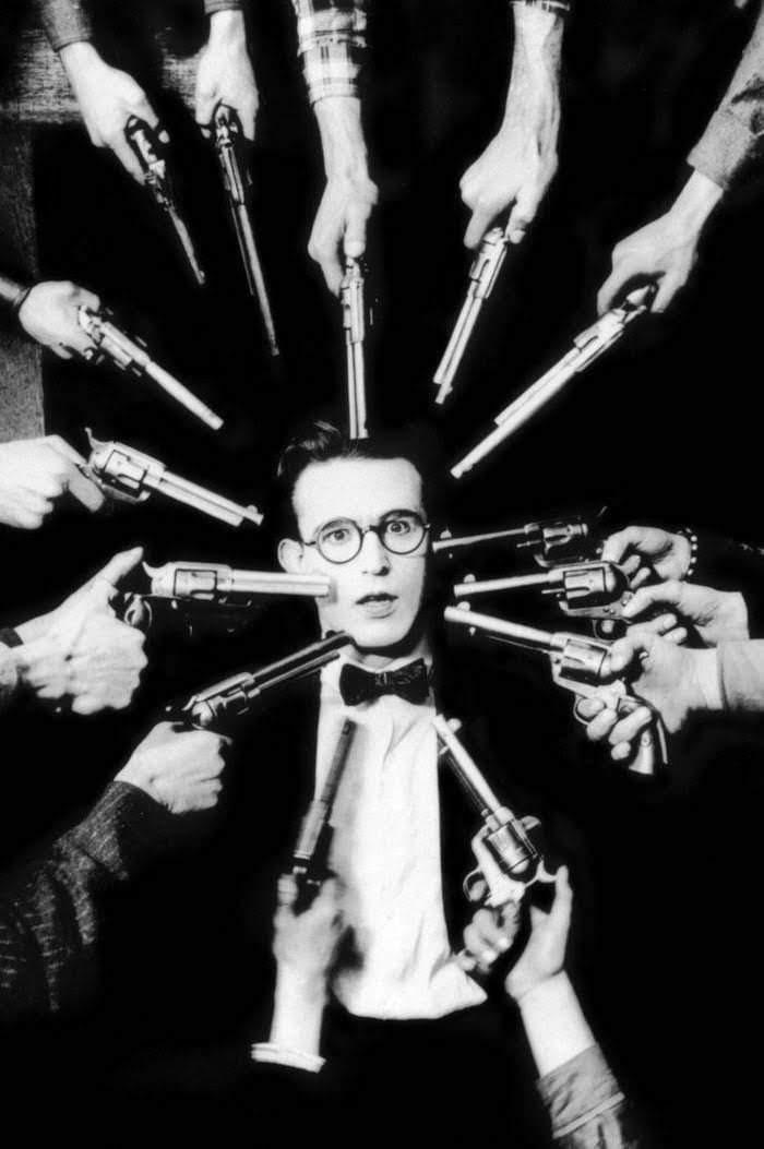 Imatge de la pel·lícula Two-Gun Gussie (1918) de Harold Lloyd on se'l veu rodejat de pistoles apuntant-lo.
