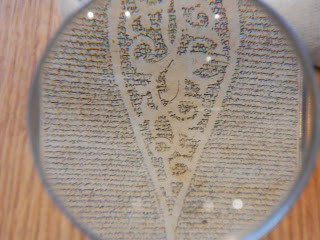 The scroll photographed through a magnifying glass, showing an abstract pattern created by the negative space in the text.