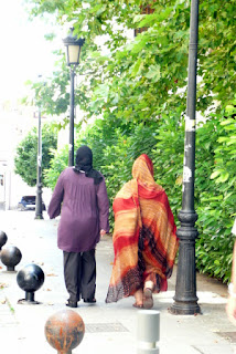 Dos mujeres musulmanas, de espaldas, caminando por una calle