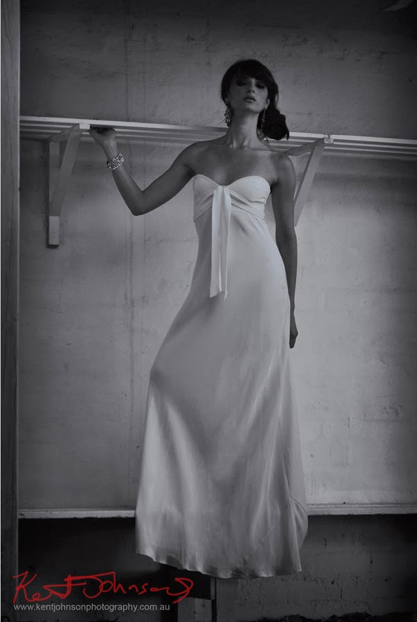 Model standing on bench, white dress against white room. Bridal dress photographed in black and white by Kent Johnson.