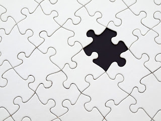 A section of a jigsaw puzzle, all of the pieces blank and white. One piece is missing.