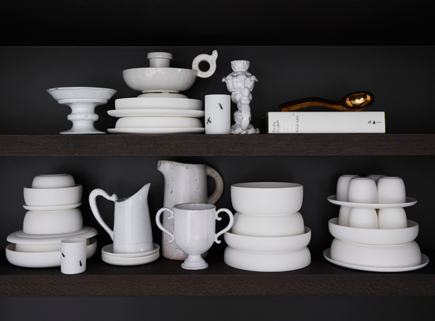 White china pottery dishes on dark shelves minimal sophisticated interior design by Piet Boon