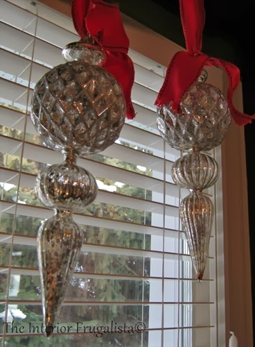 Merecury glass finials hanging by ribbon in the window