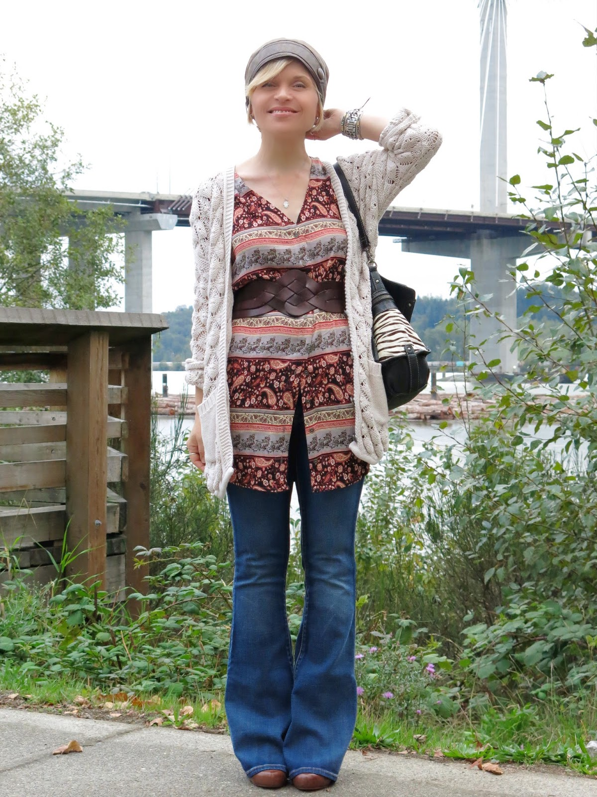 styling flare jeans with a belted floral tunic, grandpa cardigan, and leather beanie