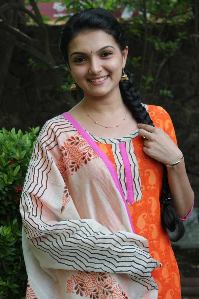 Actress Saranya Mohan Long Hair Stills In Orange Dress
