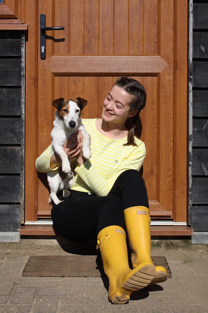 Abbey, wearing a yellow stripe top, sits on a doorstep holding Buddy, a Jack Russell terrier