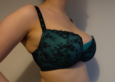 A photo of someone wearing a bra. It is difficult to make out some areas as they are in shadow.