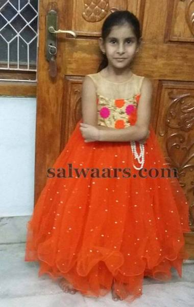 7ecda5c576 Bright orange net kids frock with cream color yoke and rose floral bunches  embellished all over