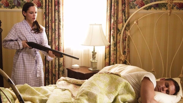 Uma mulher segurando uma espingarda calibre 12 apontada para o seu