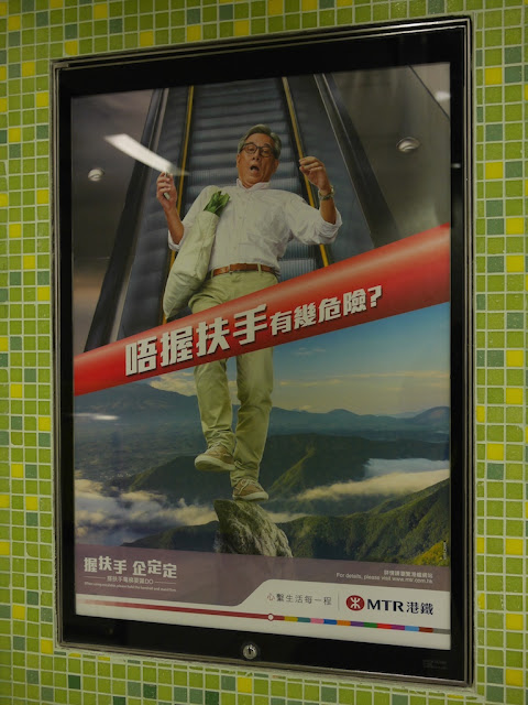 a hold the handrail MTR sign with a man perilously standing on a high rock