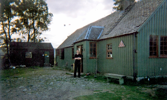 A man standing outside Loch Ossian youth hostel