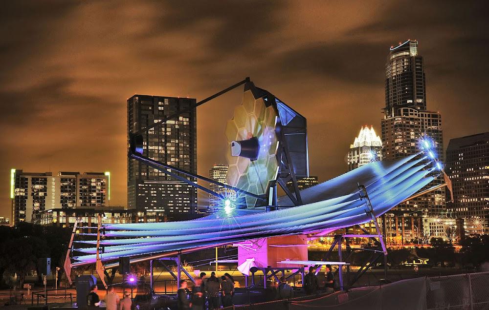 """Mô hình Kính Viễn vọng Không gian James Webb với kích cỡ đúng như thực tế được trưng bày ở Liên hoan South by Southwest ở Austin, Texas vào ngày 8 tháng 3 năm 2013. """"Đây là lần đầu tiên công chúng được biết chiếc kính này to lớn đến dường nào. Mô hình này thu hút tất cả mọi người tham dự SXSW năm đó,"""" Gunn cho biết."""