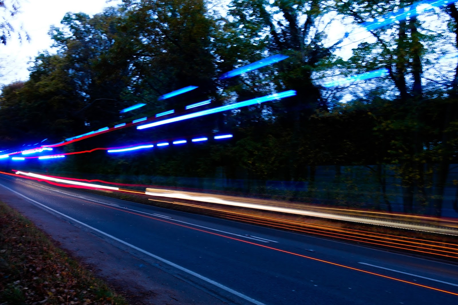 A road at dusk with lines across the photograph caused by cars and a fire engine driving past on a slow shutter speed. The lights are orange, red and blue