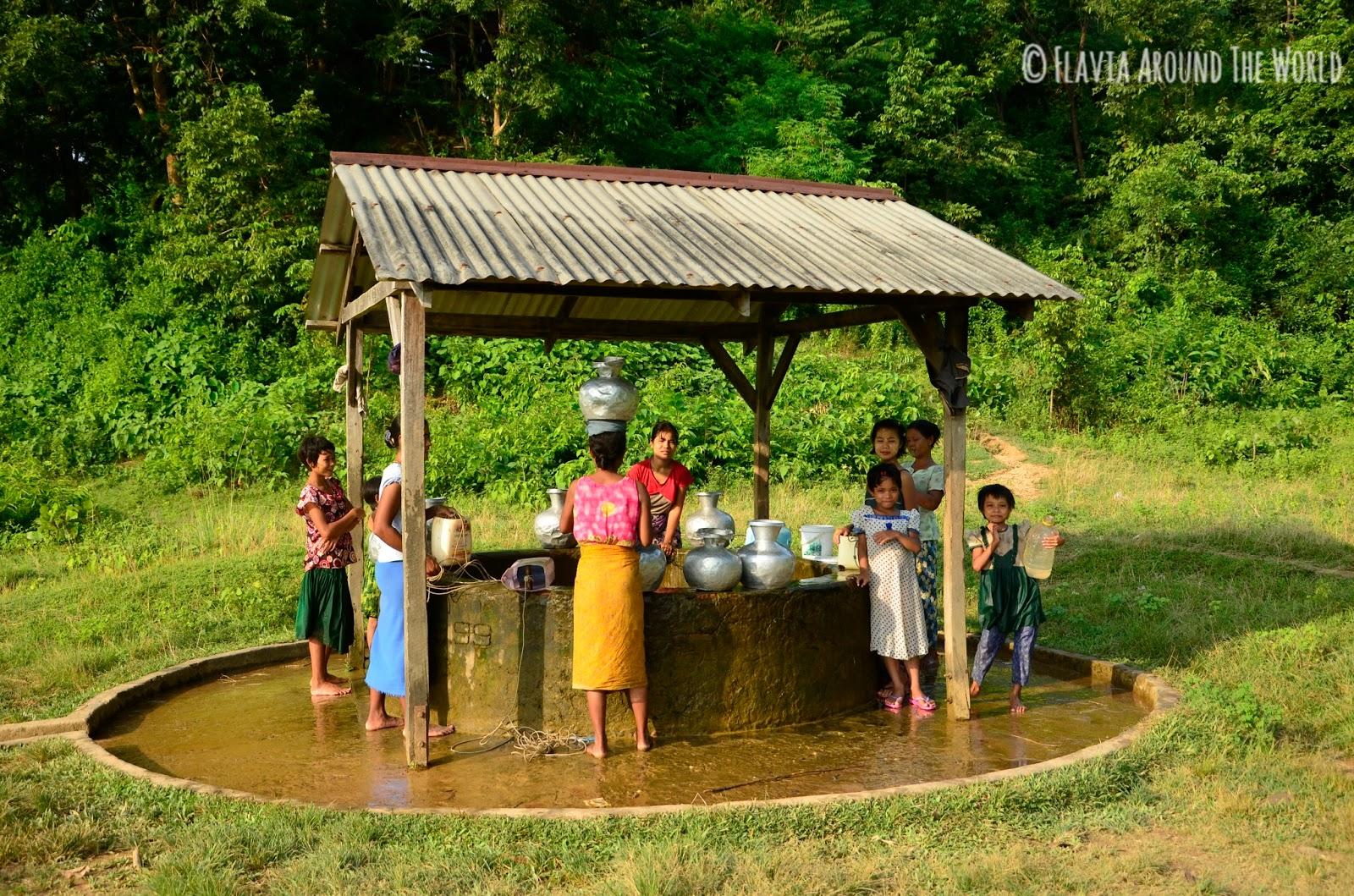 Mujeres y niñas cogiendo agua del pozo en Mrauk U
