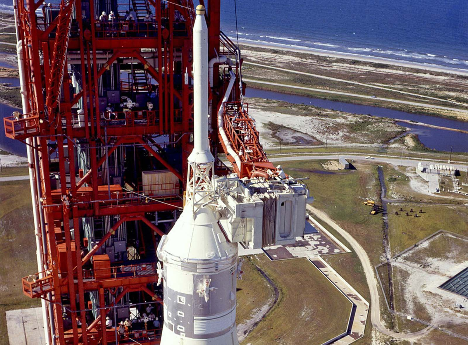 Readying for launch, a technician works atop the white room, through which the astronauts will enter the spacecraft, alongside the 363-foot (111-meter) Saturn V rocket standing on the launchpad at Kennedy Space Center.