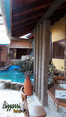 Detalhe da varanda com os pilares de pedra, as paredes de pedra com as mesas e as cadeiras de madeira e os pilares de pedra de granito cinza com o lago de carpas com a execução do paisagismo.