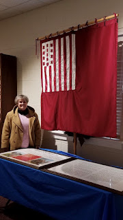 Woman in tan coat stands to left behind a table, there is a red and white Rev War era flag hanging from the ceiling