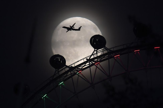 Một chiếc máy bay đang bay ngang Mặt Trăng trên bầu trời cùng vòng đu quay ở thủ đô London, Vương quốc Anh. Hình ảnh: Toby Melville/Reuters.