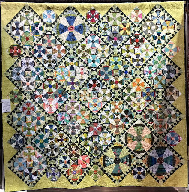 Steam Punk quilt blocks grouped in fours with sawtooth sashing of dark blue and white is bordered with chartreuse