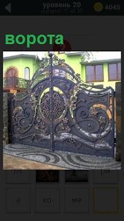 При входе в частный дом висят ажурные ворота, сделанные из железа