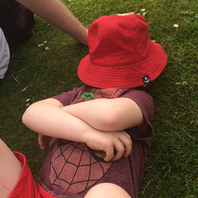 A little boy laying on the grass with his arms folded
