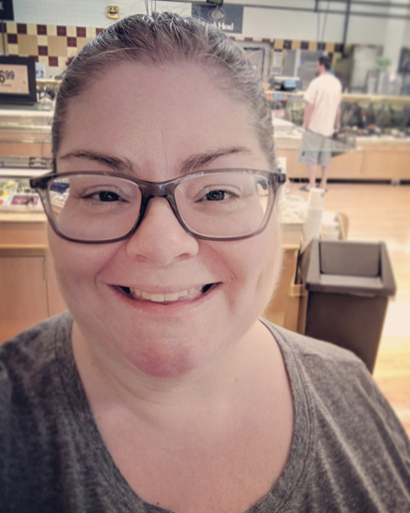 image of me in a grocery store, pictured from the shoulders up, smiling broadly, with my hair pulled back in a bun and wearing grey-framed glasses and a grey t-shirt
