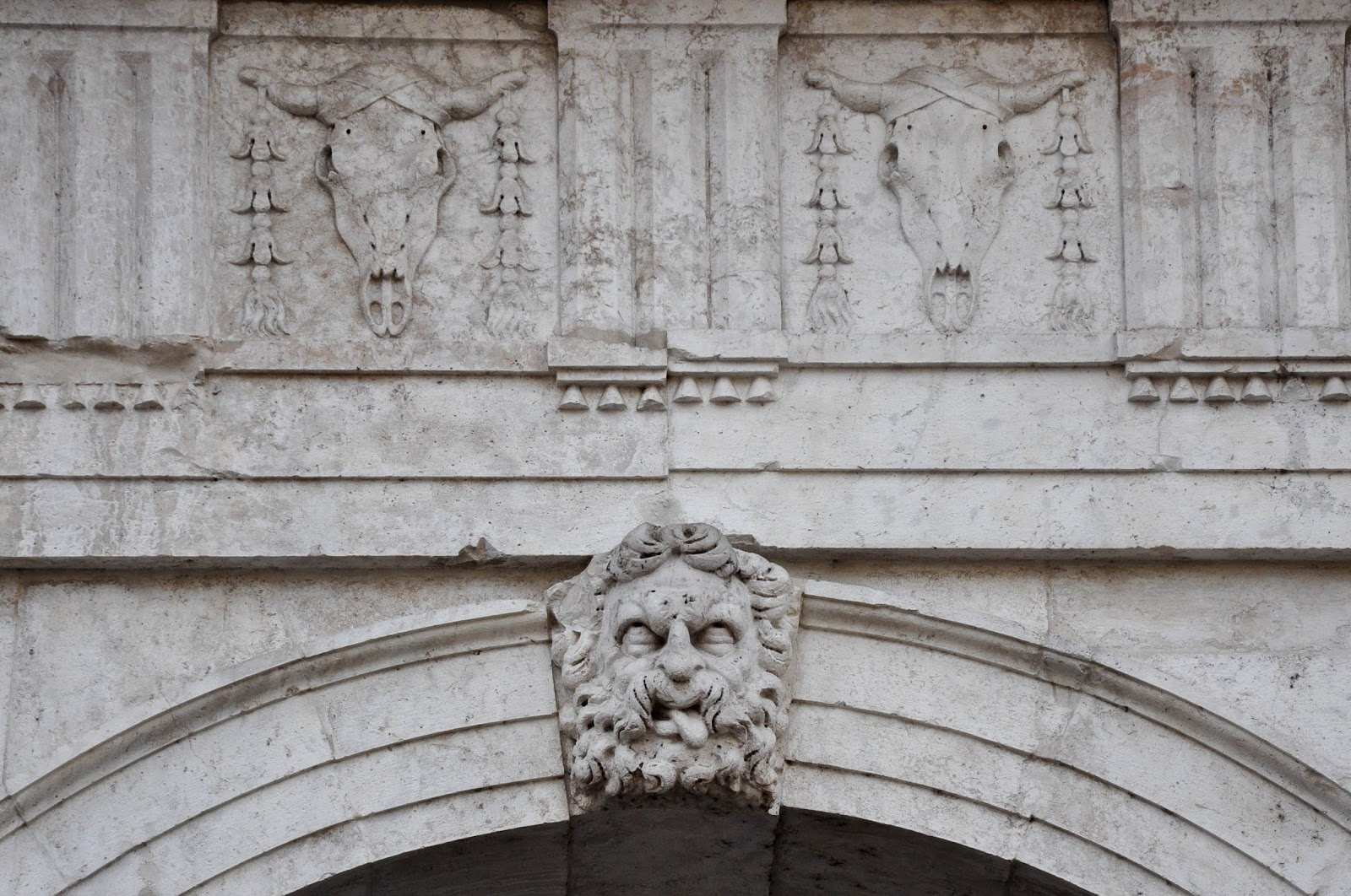 A face and two skulls on the facade of Palladio's Basilica in Vicenza, Veneto, Italy