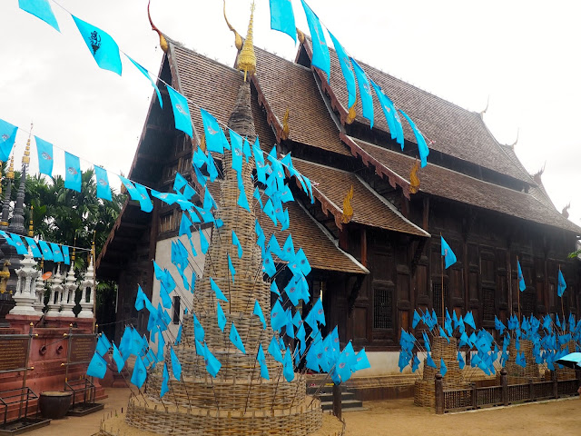 Wat Phan Tao exterior with blue flags in Chiang Mai, Thailand