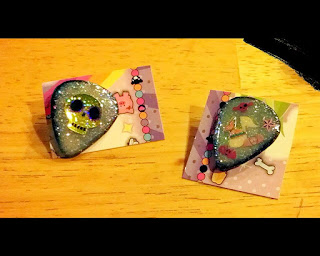 Glittery guitar pick pins, one with a skull the other with a music note and stickers