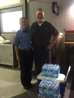 Dr. Kitzmiller stands with a member of the Apex EMS with cooler and water bottles.