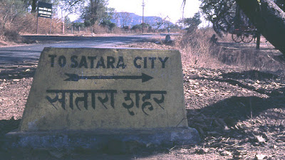 Sign written on stone by side of road in India