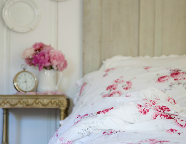 Shabby Chic floral bedding on bed in cottage