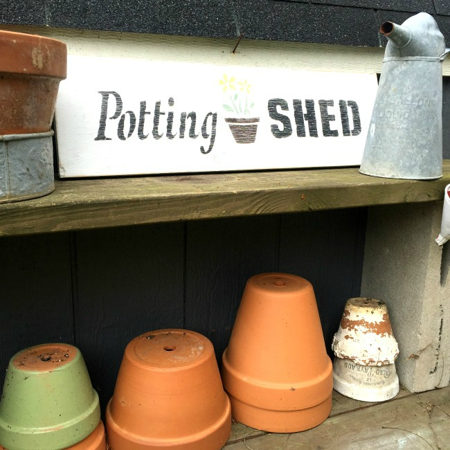 Potting shed sign on shelf with pots