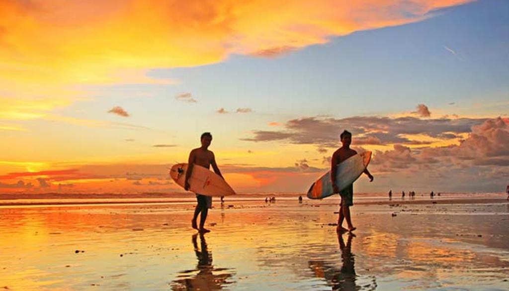 Favehotel Penginapan Dekat Pantai Kuta  Hello Beauty Escaper! Jangan katakan kalau kamu sudah pernah ke Bali tapi belum mengunjungi Pantai Kuta? Kalau belum mengunjungi Pantai Kuta sepertinya kamu harus merencakan perjalanan ke dua kamu ke Bali. Karena tempat wisata yang satu ini merupakan salah satu ikon wisata pantai di Bali.   Tidak hanya terkenal dikalangan wisatawan domestik, wisatawan mancanegara pun banyak sekali yang sudah mengincar pantai Kuta untuk kemudian dijadikan tempat menghabiskan waktu liburan.  Pantai yang berada di pesisir selatan Bali ini, akan menyuguhkan keindahannya kepada para wisatawan yang datang. Garis pantainya mempunyai panjang sekitar 2 kilometer dengan bentuk lengkung menyerupai bulan sabit. Hamparan pasir putih, deretan pohon kelapa serta deburan ombak yang begitu khas adalah salah satu hal yang wajib kamu nikmati dan abadikan.  Memasuki kawasan pantai kamu akan melihat lalu-lalang wisatawan membawa papan selancar, karena memang tempat ini cukup dikenal sebagai tempat untuk melakukan olah raga air untuk para peselancar, baik yang masih pemula atau yang sudah mahir sekalipun. Tak jarang juga pantai ini dijadikan tempat untuk diadakannya lomba berselanjar tingkat internasional.    Para Peselancar Pantai Kuta Berada di Bawah Keindahan Sunset Kuta Sumber gambar : water-sport-bali.com  Selain terkenal dengan tempat berselancar, pantai ini juga dikenal dengan pemandangan matahari terbenamnya. Kamu bisa menikmati keindahan matahari terbenam di pantai ini dengan ditemani segarnya es kelapa muda. Jangan lupa juga untuk mengabadikan momennya ya ☺  Tidak hanya disitu saja traveler, kamu juga bisa melakukan mandi matahari atau berjemur dengan ditemani tukang pijat yang dengan mudah bisa kamu panggil karena banyak sekali tukang pijat yang siap memanjakan kamu ketika berada di Pantai Kuta.  Selain dipijat dan berjemur, hal menarik selanjutnya yang bisa kamu coba adalah kepang rambut dan juga tato temporer. Sembari bersantai di pesisir pantai, kamu 