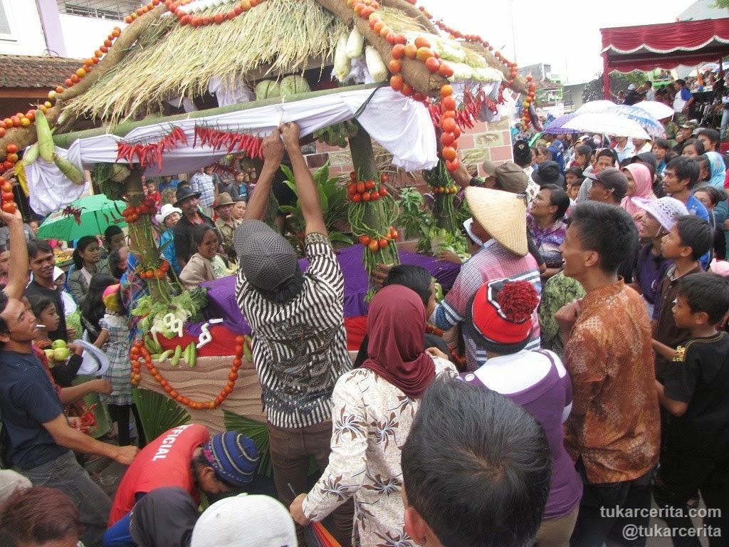 Manusia Indonesia berebut buah dan sayuran dari mobil hias karnaval