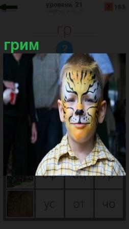 На лице у мальчика сделан грим в виде изображения тигра