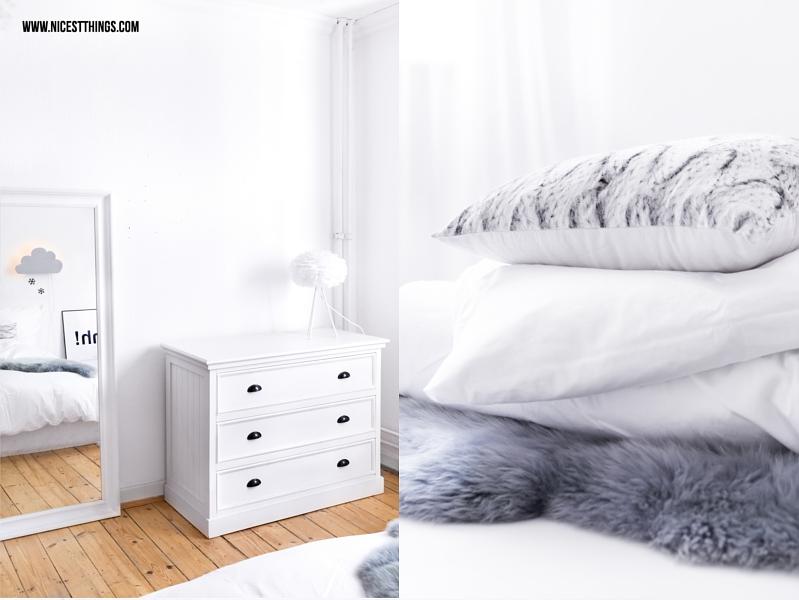 Spiegel im Schlafzimmer und grauer Kissenstapel