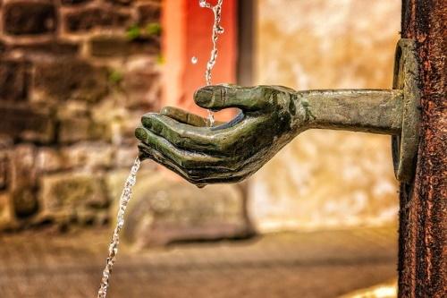 Fonte, detalhe de mão derramando água. #PraCegoVer