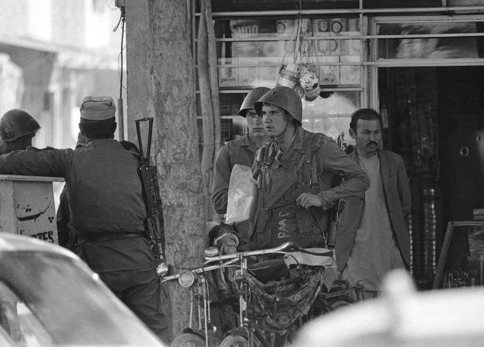 Two Soviet Army soldiers emerge from an Afghan shop in downtown Kabul on April 24, 1988.