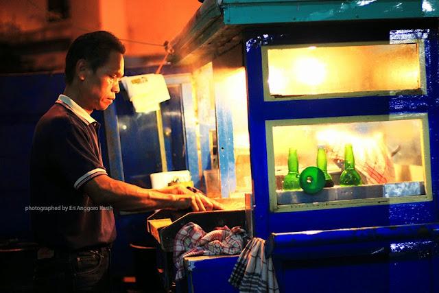 Kang Hendi sedang melayani pembeli mie kocok