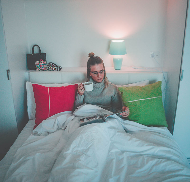 girl in hotel bed drinking coffee and reading magazine instagram fashion travel blogger